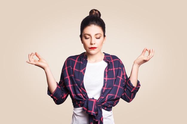 명상, 종교 및 영적 실천. 아침에 실내에서 베이지색 벽에서 요가를 하는 아름다운 젊은 브루네트 소녀, 눈을 감고 무드라 제스처로 손가락을 잡고