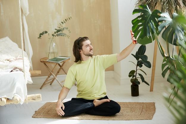 Meditation teacher in lotus pose holding phone, yoga man at home doing selfie on fitness mat