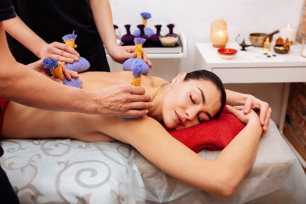 Meditative session. good-looking naked woman being satisfied with quality of work while masseuses processing her back