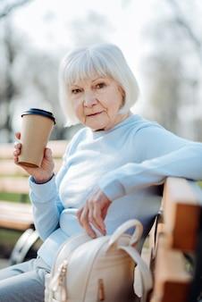 명상. 벤치에 앉아있는 동안 커피를 마시는 사려 깊은 금발 여자