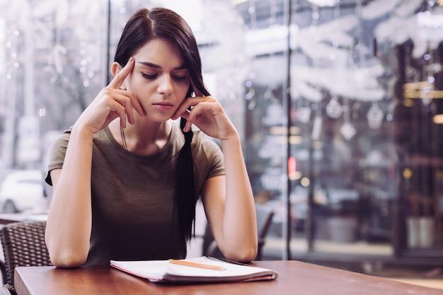 Медитативная вдумчивая студентка массирует виски, закрывая глаза и сидя перед тетрадью