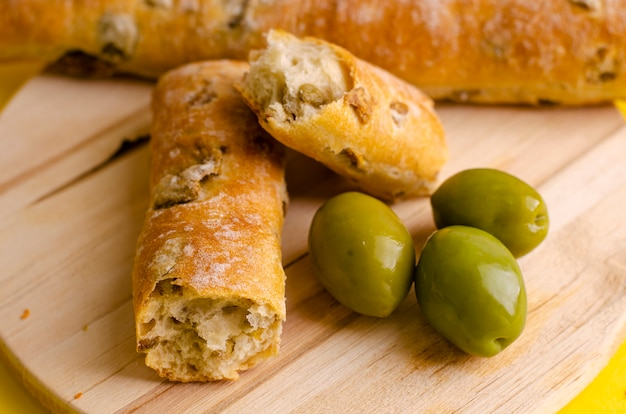 Mediterranean bread stuffed with green olives on wooden cutting board