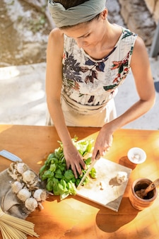 Mediterranean brunette woman preparing genoese pesto sauce on a wooden table seen from above