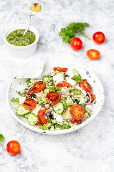 Mediterranean couscous salad with fried cherry tomatoes, cucumber and pesto sauce
