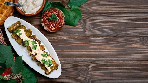地中海料理、暗い木製のテーブルにコリアンダーとソースを添えたプレートのドルマ、コピースペースのある上面図。ドルマ、肉とブドウの葉の伝統的な料理-白人、トルコ料理、ギリシャ料理