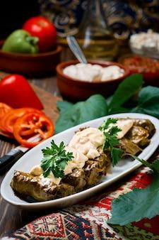 地中海料理-暗い木製のテーブルに新鮮なコリアンダーとソースを添えたプレートのドルマ、クローズアップの側面図。ドルマ、肉とブドウの葉の伝統的な料理-白人、トルコ料理、ギリシャ料理