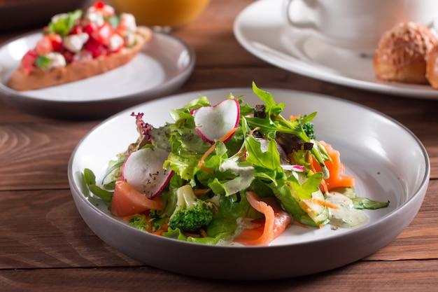 Mediterranean cuisine. salad. slices of salmon with fresh vegetable salad on a plate.