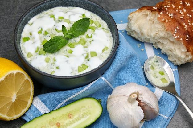 지중해 요리. 콘크리트 테이블에 어두운 그릇에 레몬과 마늘을 넣은 신선한 오이, 민트, 요구르트로 만든 짜 치키 소스