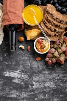Mediterranean food drinks ingredients set for dinner. wine honey cheese nuts snacks bread grapes fruit on dark black stone background with copy space. gastronomy natural food and drink products.
