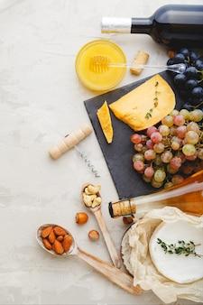 지중해 음식 음료 재료 저녁 식사를 위해 설정합니다. 와인 꿀 치즈 견과류 스낵 빵 포도 과일은 밝은 회색 돌 배경에 있습니다. 요리법 자연 식품 및 음료 제품.