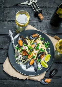 Средиземноморская кухня. спагетти из морепродуктов с моллюсками и белым вином. на черном деревенском фоне.