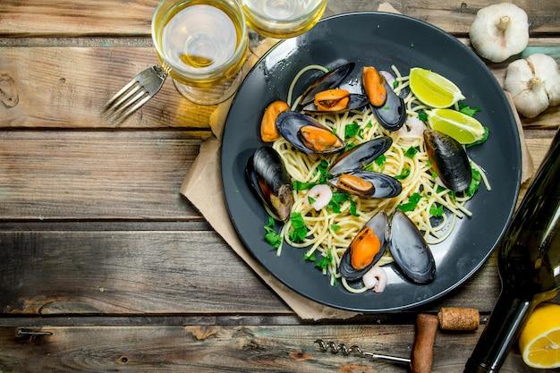 Средиземноморская кухня. спагетти из морепродуктов с моллюсками и белым вином. на деревянном фоне.