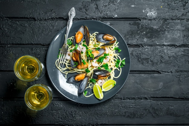 Mediterranean food. seafood spaghetti with clams and white wine. on a black rustic background.
