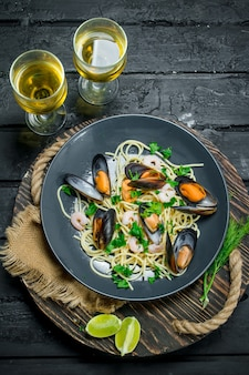 Mediterranean food. seafood spaghetti with clams and white wine on dark rustic table.