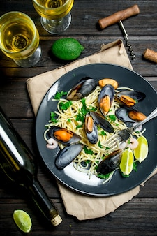 Mediterranean food. seafood spaghetti with clams and white wine on a rustic table.