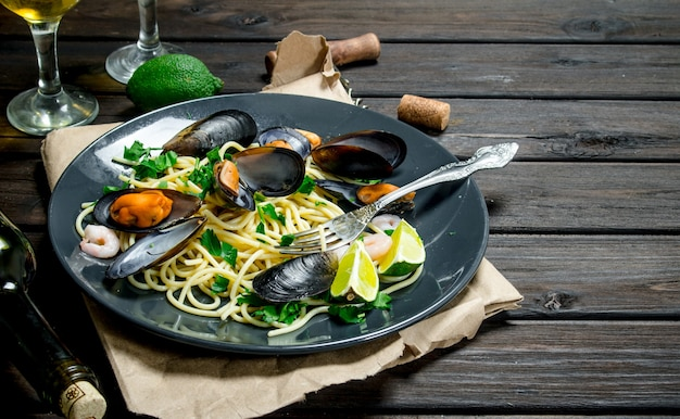 Mediterranean food. seafood spaghetti with clams and white wine. on a wooden background.