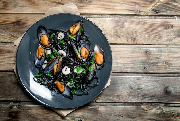 Средиземноморская кухня. спагетти с черными чернилами каракатицы и моллюсками. на деревянном фоне.