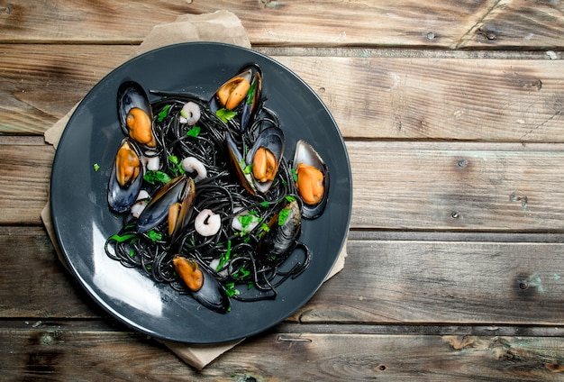 Mediterranean food. spaghetti with cuttlefish black ink and clams. on a wooden background.
