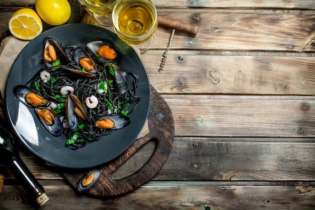 Средиземноморская кухня. спагетти с чернилами каракатицы, моллюсками и белым вином. на деревянном фоне.