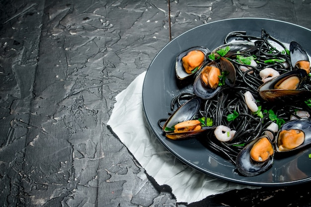 Mediterranean food. spaghetti with cuttlefish ink and clams on rustic table.