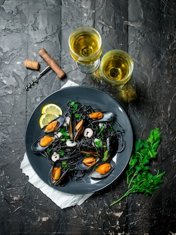 Mediterranean food. spaghetti with cuttlefish ink, clams and white wine. on black rustic background.