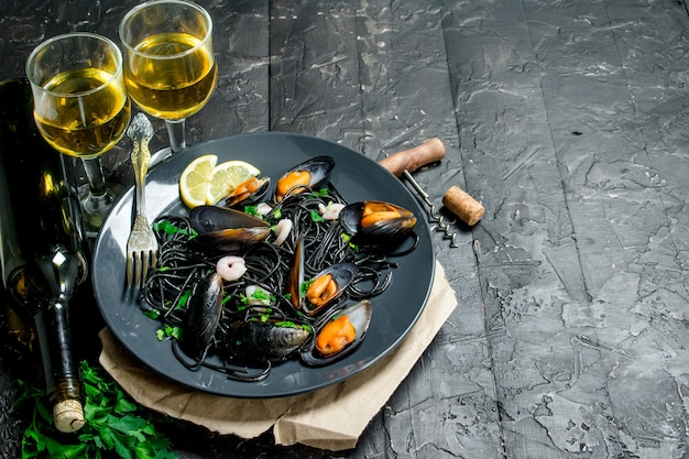 Mediterranean food. spaghetti with cuttlefish ink, clams and white wine on black rustic table..