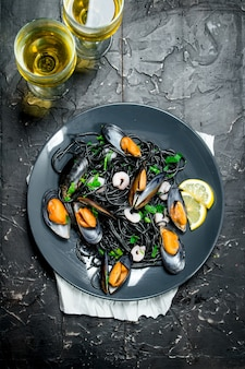 Mediterranean food. spaghetti with cuttlefish ink, clams and white wine. on black rustic.