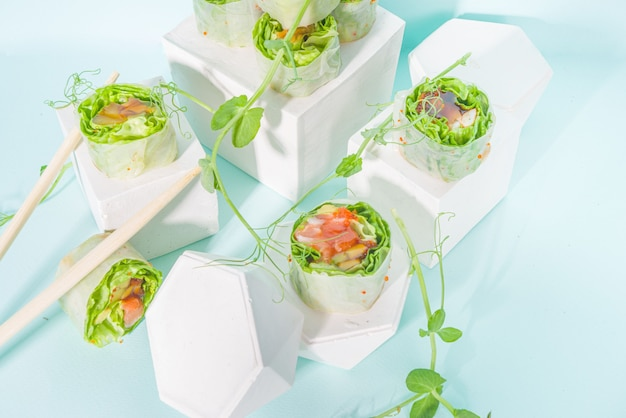 Концепция средиземноморской, нордической и кето-диеты. суши без риса, диетическое питание с морепродуктами, овощами. модные азиатские спринг-роллы в стиле суши на синем современном фоне