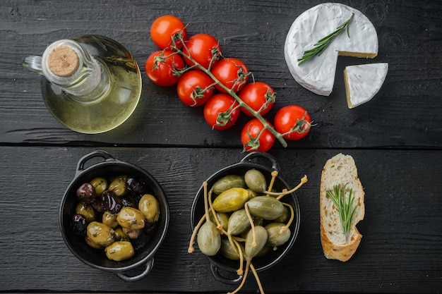 Mediterranean olives and capers with herbs, on black wooden table, top view