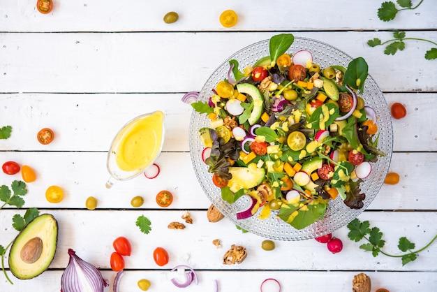 흰색 나무 바탕에 노란색 소스를 곁들인 지중해식 유기농 신선한 샐러드