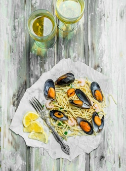 Mediterranean pasta. spaghetti seafood, clams and white wine. on a rustic table.
