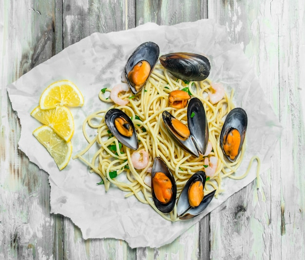 Mediterranean pasta. spaghetti seafood with clams on paper. on a rustic table.