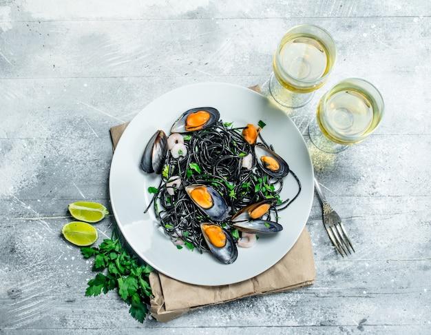 Средиземноморская паста. спагетти с чернилами каракатицы, моллюсками и белым вином. на деревенском фоне.