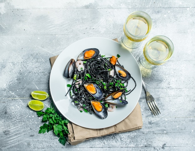 Mediterranean pasta. spaghetti with cuttlefish ink, clams and white wine. on a rustic background.