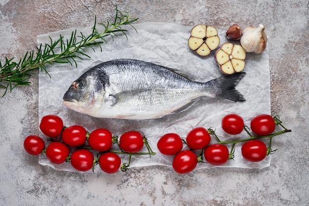 지중해 해산물 개념. 테이블에 마늘, 토마토, 로즈마리와 원시 황새 물고기. 신선한 유기농 도미 또는 도라다 생선. 평면도, 복사 공간