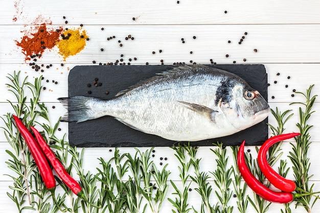 地中海のシーフードのコンセプト。白い木製のテーブルにコショウとローズマリーと生のドラド魚。コピー