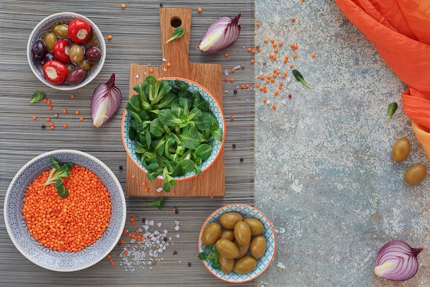 地中海スナックセット。緑と黒のオリーブ、焼きたてのマルチグレインパン、コーンサラダ、古い木の背景に赤玉ねぎ。テキスト用のスペースのある上面図