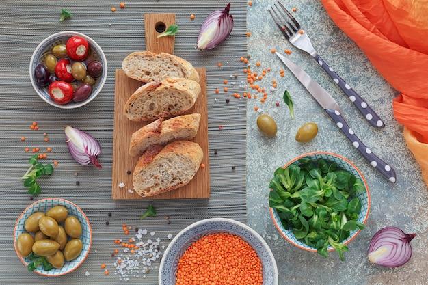 地中海スナックセット。緑と黒のオリーブ、焼きたてのマルチグレインパン、赤のスプリットレンズ豆、コーンサラダ、古い木の背景に赤玉ねぎ。テキスト用のスペースのある上面図