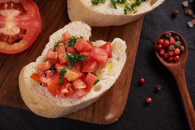 지중해 식 간식 세트. 올리브, 오일, 허브 및 어두운 표면 위에 검은 슬레이트 돌 보드에 나무 보드에 얇게 썬 ciabatta, 신선한 빵에 육즙 토마토, 토핑으로 페스토. 평면도. 플랫 레이