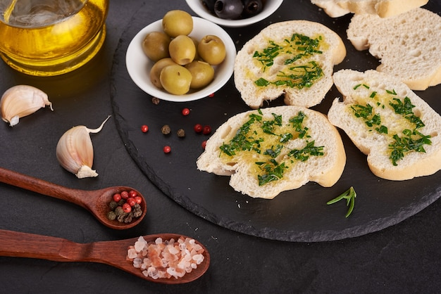 Mediterranean snacks set. olives, oil, herbs and sliced ciabatta bread on black slate stone board over painted dark blue surface, top view. flat lay.