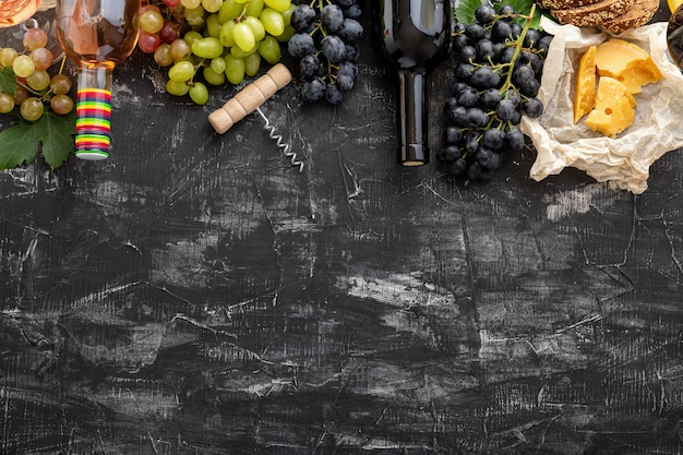 Mediterranean wine drinks and food ingredients long web banner. different rose red wines in bottles. wine grapes fruit aged cheese corkscrew on dark black stone. gastronomy natural food drink.