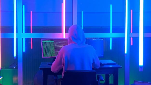 Средний снимок сзади: преступный хакер, работающий вечером на компьютере в большом офисе с теплым ...