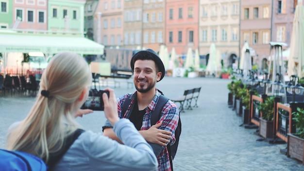 Средний крупный план пары туристов, делающих фотографии с фотоаппаратом на исторической рыночной площади. мужчина позирует и женщина фотографирует.