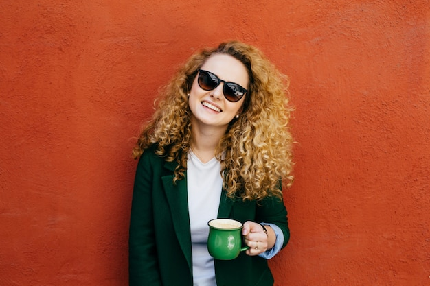 Medium close-up of pleased pretty woman with curly hair wearing sunglasses and jacket.