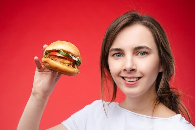 신선한 식욕을 돋우는 샌드위치를 물고 있는 아름다운 젊은 패션 여성의 중간 클로즈업 초상화. 카페에서 패스트푸드를 즐기며 포즈를 취하는 사랑스러운 여성의 초상화