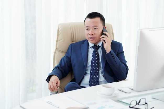 Medium closeup of asian businessman making a phone call seated at his office desk