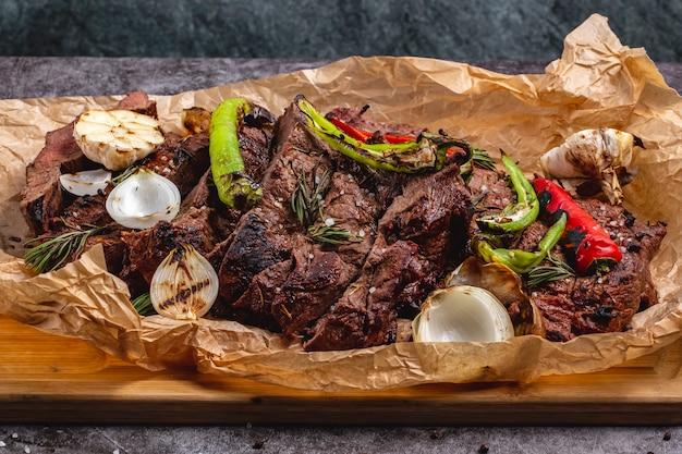 Средне приготовленный стейк с чесноком, красным луком и перцем чили на пергаментной бумаге
