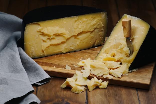 Сырная головка средней твердости с пармезаном на деревянной доске с ножами для сыра с пармезаном