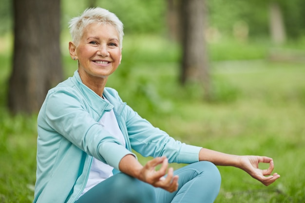 Medium long portrait of senior woman spending morning time sitting on grass in park meditating