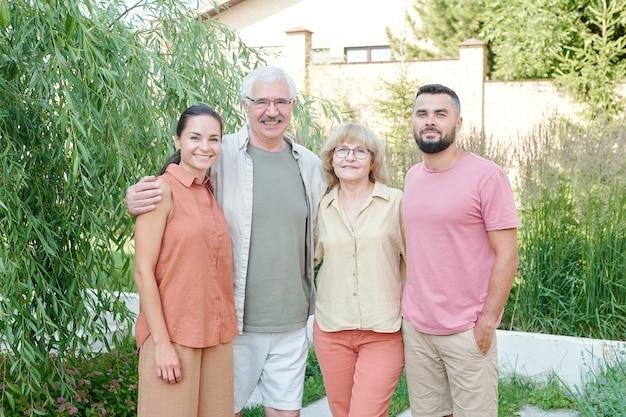 夏の日に屋外で一緒に立っている先輩の両親とその若い成人した子供たちのミディアムショットの家族の肖像画